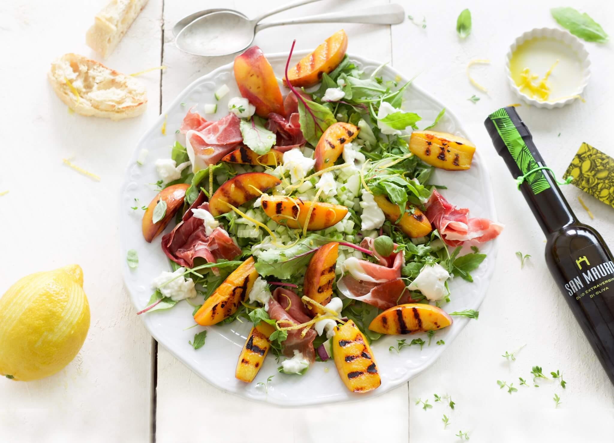 Salade met mozzarella, perzik, Parmaham en citroenolijfolie