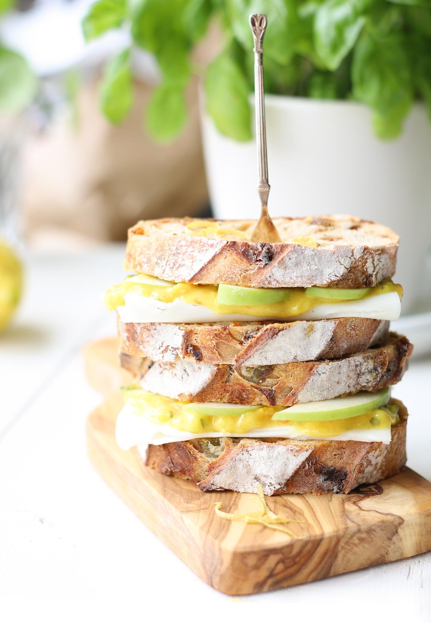 Lunchtijd, wat kan ik daar elke dag weer blij van worden. Vaak heb je dan al een paar uur gewerkt en hteb je weer energie nodig. Als ik brood eet, eet ik het liefste notenbrood of zuurdesem. Dit heeft tenminste smaak en sterructuur! DezeGeitenkaas sandwiches met appel & piccalillyheb ik gemaakt met vers notenbrood. Wist je dat je piccalilly heel makkelijk zelf maakt? Ik heb laatst er een met extra gember gemaakt en binnenkort vertel ik je graag hoe je dit precies maakt! Geitenkaas sandwiches met appel & piccalilly Bereidingstijd: 15 minuten voor 2 personen Ingrediënten 1 groene appel 4 eetlepels piccalilly *Kesbeke bijvoorbeeld notenbrood *bij de bakker of sommige supermarkten zachte geitenkaas *Président Rondélé is mijn favoriet 1 biologische citroen kruidenzout Benodigdheden Handrasp Broodrooster of oven Bereidingswijze geitenkaas sandwiches met appel & piccalilly Als eerste ga je de groene appel in dunne plakjes snijden, verdeel hier vervolgens wat verse citroensap overheen zodat ze lekker vers, knapperig en fris blijven. Vervolgens rooster je het notenbrood even in de oven of een broodrooster en zorg ervoor dat ze lekker krokant worden. Laat ze even afkoelen en smeer ze daarna ruim in met de zachte geitenkaas, vervolgens de dunne groene schijfjes appel en daarna piccalilly naar smaak. Vergeet niet wat kruidenzout, verse kruiden zoals tuinkers of basilicum toe te voegen en eventueel wat zwarte peper kan lekker zijn. Als laatste rasp je nog wat citroenzest eroverheen en je Avocado sandwiches met geitenkaas, appel & piccalilly zijn klaar! Tip: wist je dat deze combinatie ook lekker kan zijn op een toastje als je bijvoorbeeld een verjaardag hebt of een feestje geeft? Volgen jullie The Lemon Kitchen al op Facebook, Instagram & Pinterest? Ben jij net zoals ik gek op sandwiches met geitenkaas? Maak dan eens hemelse Lemoncurd sandwiches met geitenkaas & avocado of zuurdesembrood met zachte geitenkaas met een frisse mango salade!